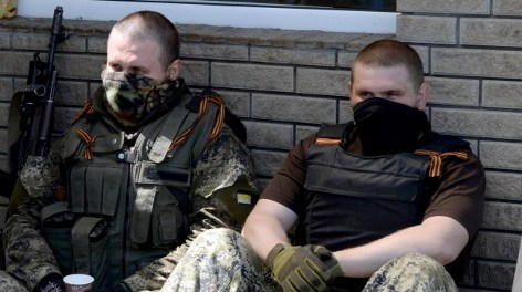 "Armed pro-Russian militants sit on the ground as they rest at their checkpoint in the village of Semyonovka near the eastern Ukrainian city of Slavyansk on May 16, 2014. The United Nations warned on May 16 of an ""alarming deterioration"" of human rights in eastern Ukraine, where an armed insurgency by pro-Russian separatists is threatening a presidential election just over a week away. In a new report, the UN's rights chief catalogued a litany of ""targeted killings, torture and beatings, abductions, intimidation and some cases of sexual harassment"" which it said was carried out by anti-government groups in the east. AFP PHOTO/ VASILY MAXIMOV"