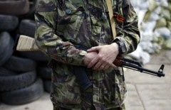 An armed pro-Russian rebel stands guard outside the town hall in Mariupol, eastern Ukraine May 4, 2014. Ukrainian Prime Minister Arseny Yatseniuk accused Russia on Sunday of engineering clashes in Odessa that led to the deaths of more than 40 pro-Russian activists in a blazing building and pushed the country closer to civil war. REUTERS/Marko Djurica (UKRAINE - Tags: POLITICS CIVIL UNREST)