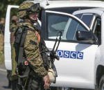 An armed pro-Russian separatist looks back next to a vehicle of the Organisation for Security and Cooperation in Europe's (OSCE) monitoring mission in Ukraine, on the way to the site in eastern Ukraine where the downed Malaysia Airlines flight MH17 crashed, outside Donetsk, July 30, 2014. REUTERS/Sergei Karpukhin (UKRAINE - Tags: TRANSPORT CIVIL UNREST DISASTER POLITICS CONFLICT)