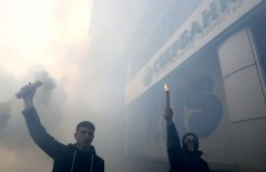 Men burn smoke flares outside a branch of Sberbank, which is the local subsidiary of Russia's largest lender, during a protest of members and supporters of the National corp political party in Kiev, Ukraine, March 13, 2017. REUTERS/Valentyn Ogirenko - RTX30SFP