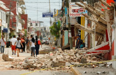 Residents walk past a building destroyed in an earthquake that struck off the southern coast of Mexico late on Thursday, in Juchitan, Mexico September 8, 2017. REUTERS/Jorge Luis Plata - RC1EB84F0ED0