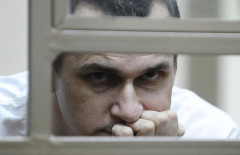 Ukrainian film director Oleg Sentsov watches from a defendants' box as he attends a court hearing in Rostov-on-Don, Russia, July 21, 2015. Sentsov was detained and accused by Russian authorities of planning to organize attacks in Crimea in May 2014, while his followers say the charge was politically motivated, according to local media. REUTERS/Sergey Pivovarov