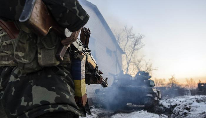 epa04544463 A picture made available 01 January 2015 shows a Ukrainian soldier looking at a tank near Peski village, Donetsk area, Ukraine, 31 December 2014, few hours before the 2015 celebrations. Ukrainian President Poroshenko on 29 December had signed a law that cancels Ukraine's non-aligned status and promised to initiate reform allowing Ukraine to comply with NATO standards as well as to hold a referendum on joining the alliance, a step opposed by Russia.  EPA/OLGA IVASHCHENKO